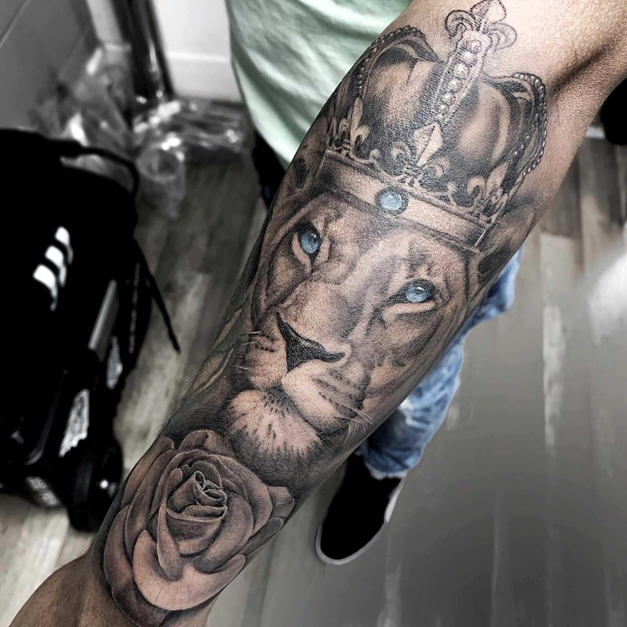 татуировка короны на руке с львом и розой