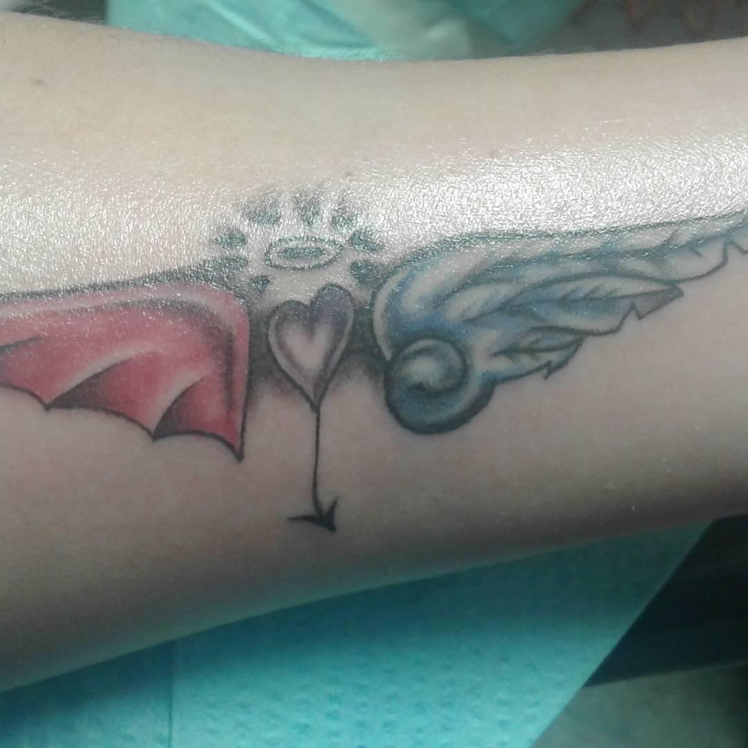 крила ангела і демона на руці