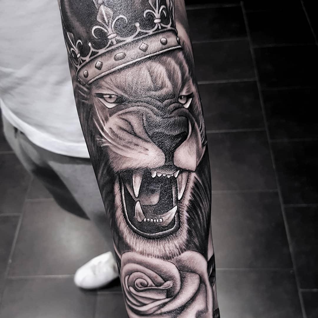 гарчащий лев з короною татуювання на руці