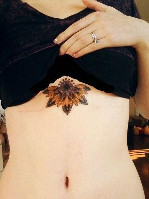 красочная татуировка подсолнуха под грудью