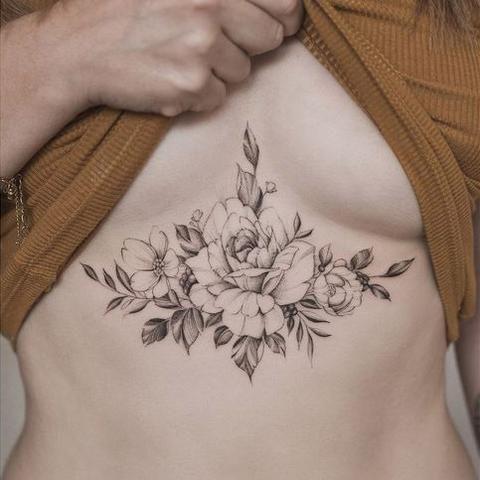 тату полевых цветов под грудью