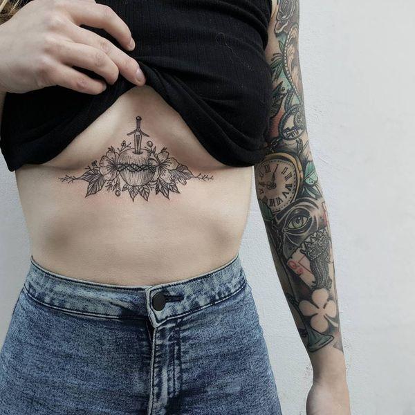 татуировка под грудью с яблоком и кинжалом
