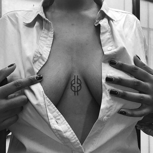 тату символа мудрости под грудью