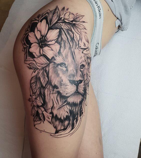 тату лева з квітами на стегні