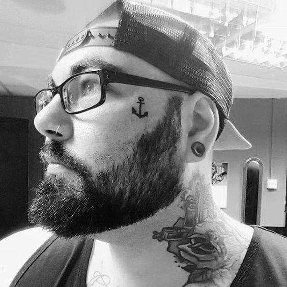 мужская татуировка якоря на лице