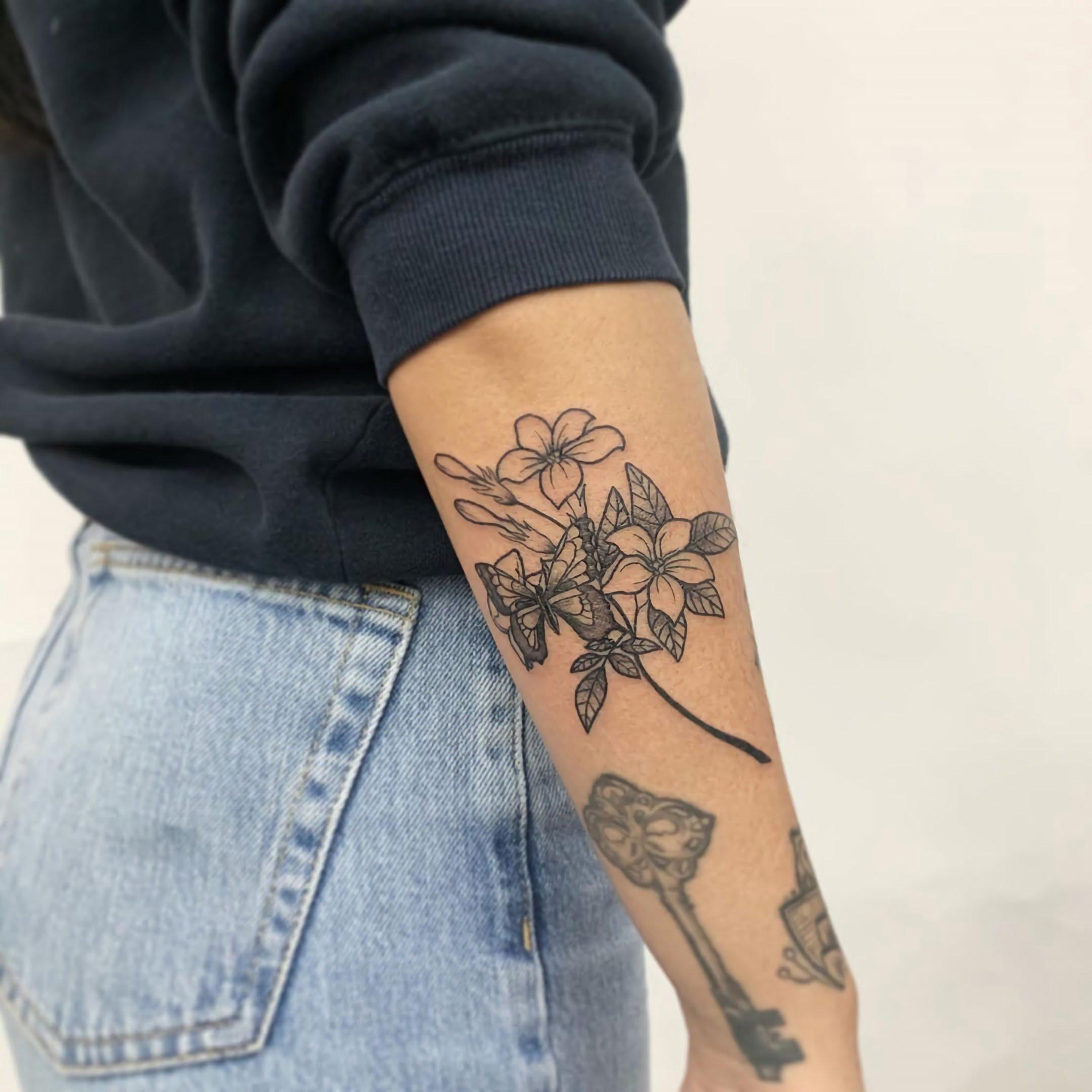 татуировка жасмина на руке девушки
