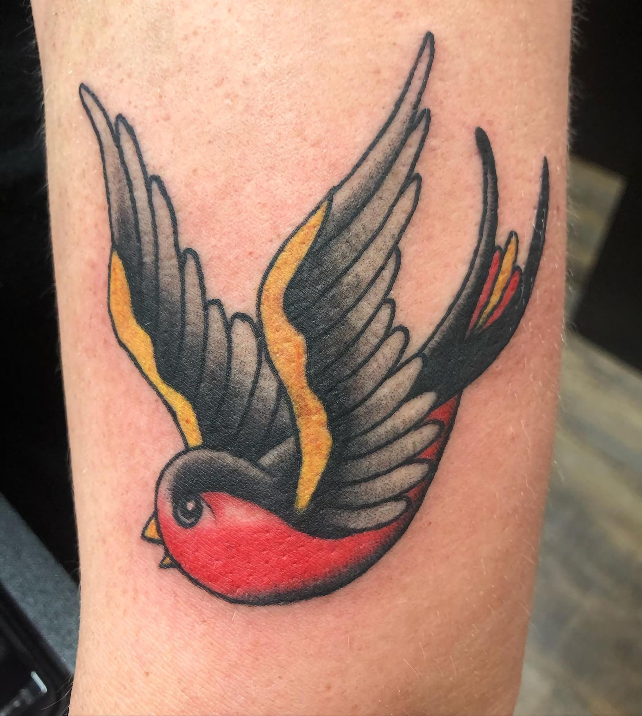 Ярко-оранжевая татуировка в виде ласточки